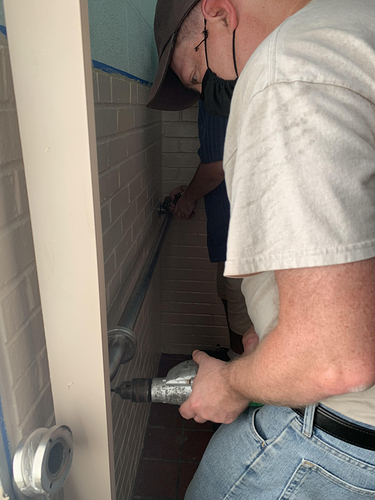 2020-07-14 - Steve S and Nick drill into brick to hang ADA grab bars in men_s bathroom at Booth